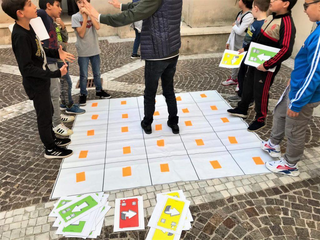 bambini che giocano con il gioco del coding unplugged e imparano termini della sostenibilità ambientale
