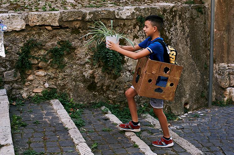 Bambini che costruiscono il Pedibus (o Piedibus) a Cori con materiale di riciclo mentre posizionano le piantine che saranno le fermate del Pedibus