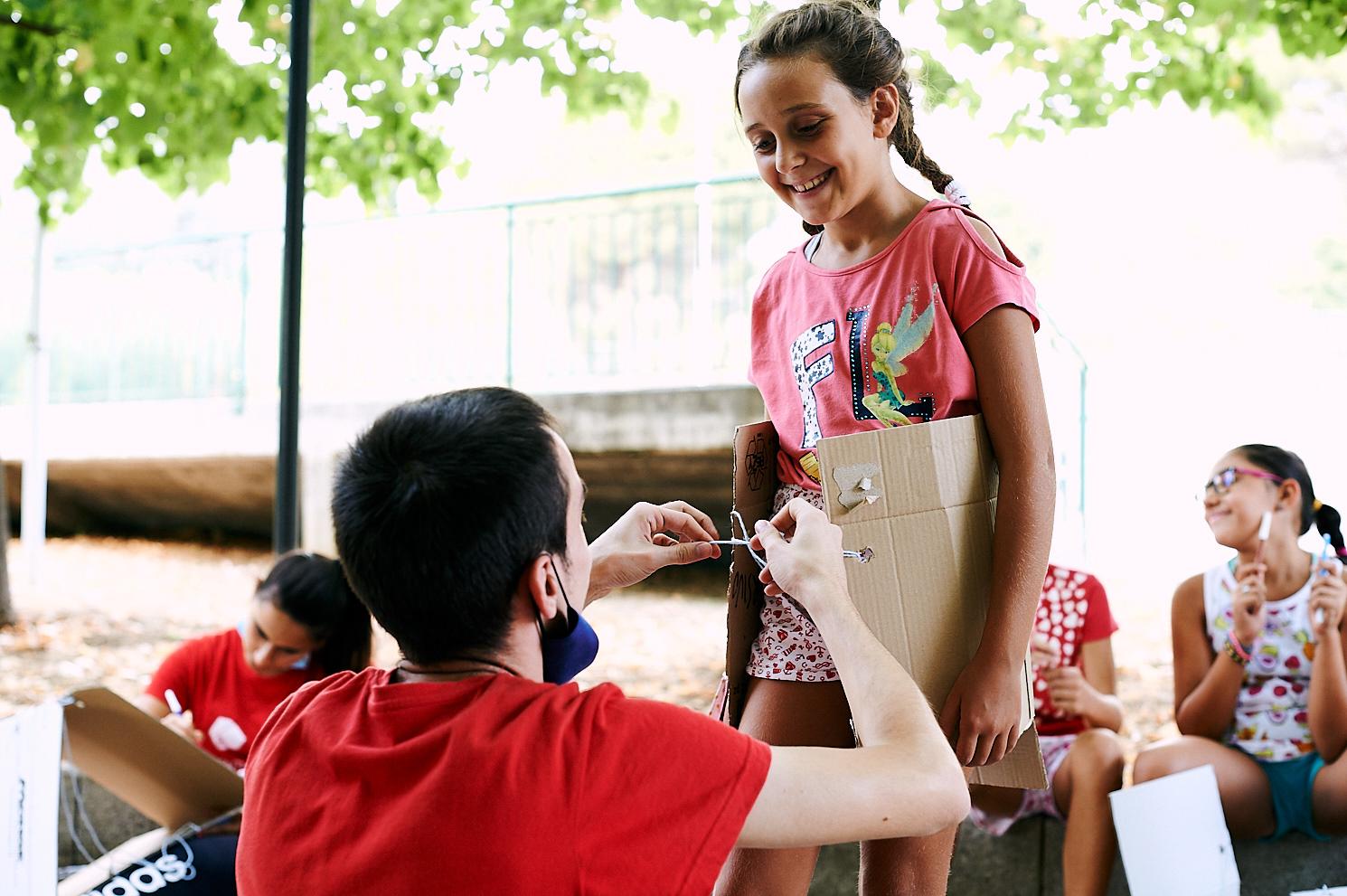 educatore aiuta bambina durante il centro estivo con materiale di riciclo